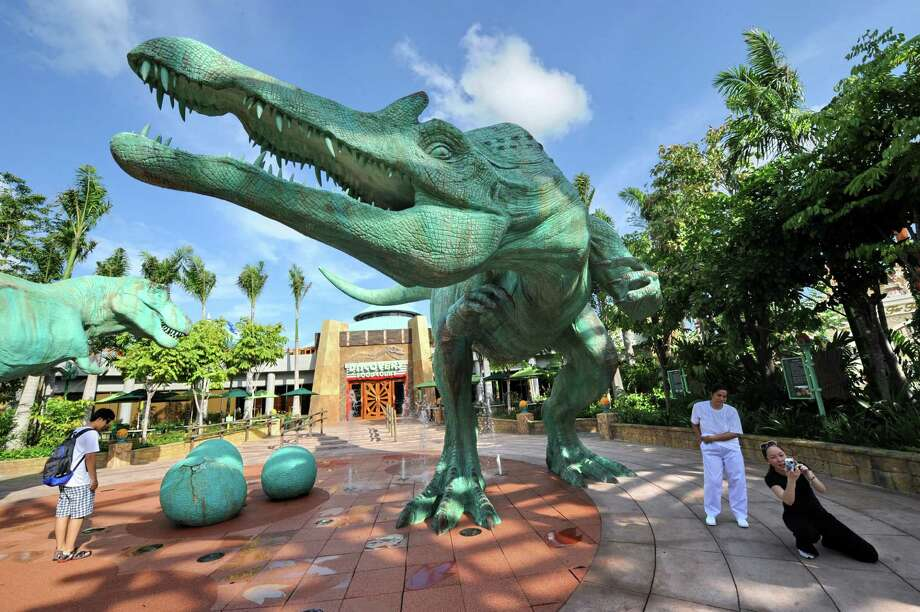 Visitors take pictures next to a dinosaur replica outside the Jurassic park attraction on the opening day of Resorts World Sentosa Southeast Asia's first Universal Studios movie theme park in Singapore on March 18, 2010. Photo: ROSLAN RAHMAN, AFP/Getty Images / 2010 AFP