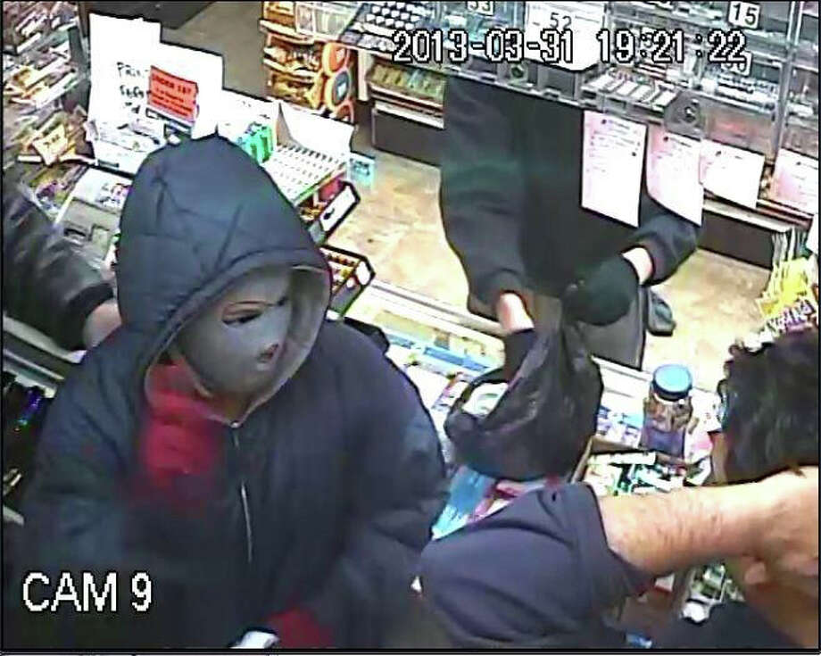 Surveillance image from a camera at the Cove Variety store at 861 Cove Road. The store was robbed by two men and a woman armed with a gun, a knife and pepper spray Sunday night. The three made off with $1,200 in cash and $500 in cigarettes. Photo: Contributed Photo