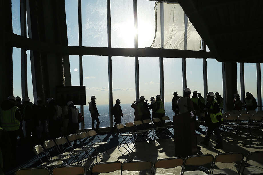 Visitors stand near the windows of the One World Observatory from the 100th floor of One World Trade Center at the Ground Zero site on April 2, 2013 in New York City. One World Observatory, which is situated more than 1,250 feet over lower Manhattan, will open to the public in 2015 and will include a pre-show theater, multiple spaces that allow for panoramas of the New York City region and numerous dining options. When completed, One World Trade Center will be the tallest building in the Western Hemisphere at 1776 feet. Photo: Spencer Platt, Getty Images / 2013 Getty Images