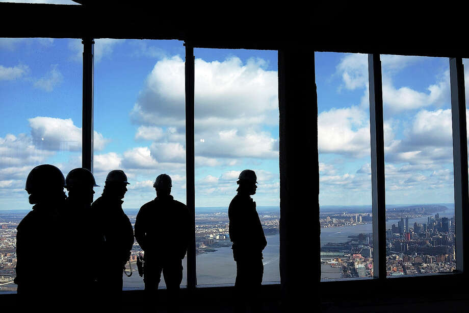 Members of the Port Authority Police stand near the windows in the One World Observatory from the 100th floor of One World Trade Center at the Ground Zero site on April 2, 2013 in New York City. One World Observatory, which is situated more than 1,250 feet over lower Manhattan, will open to the public in 2015 and will include a pre-show theater, multiple spaces that allow for panoramas of the New York City region and numerous dining options. When completed, One World Trade Center will be the tallest building in the Western Hemisphere at 1776 feet. Photo: Spencer Platt, Getty Images / 2013 Getty Images