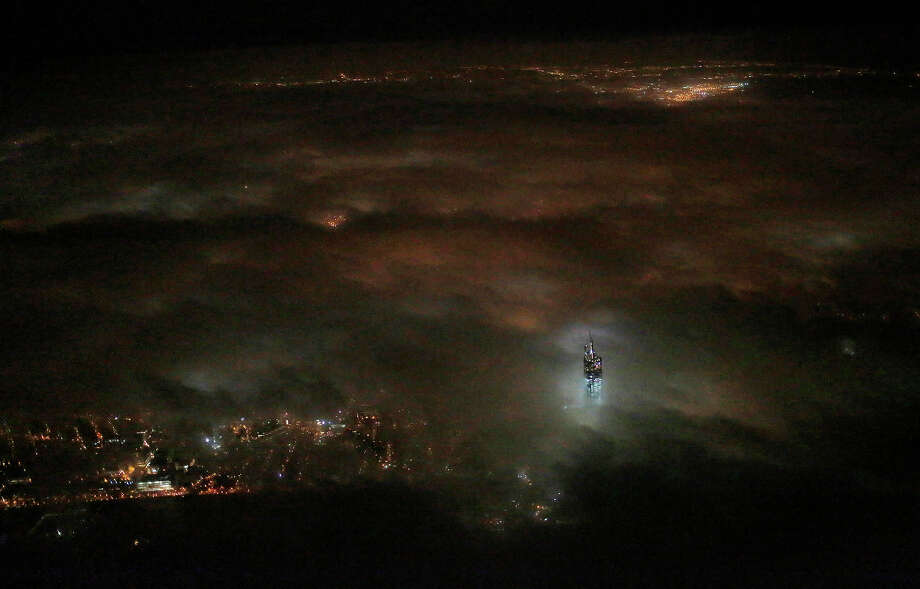 One World Trade Center emerges from the clouds in the night sky in a photo made from a passing airplane, Monday, March 12, 2013 in New York. Photo: Matthew Ziegler, ASSOCIATED PRESS / AP2013