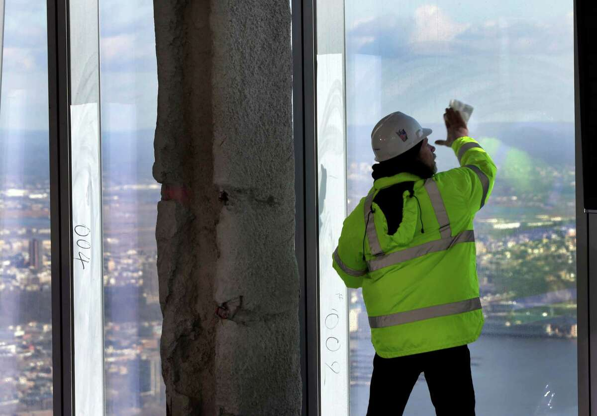A Port Authority worker cleans a window of the unfinished observation deck on the 100th floor of the One World Trade Center building, under construction in New York, Tuesday, April 2, 2013. The observation deck will occupy the tower's 100th through 102nd floors. Elevators will whisk visitors to the top in just one minute but the experience of visiting the attraction will take an hour.