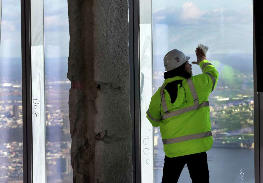 A Port Authority worker cleans a window of  the unfinished observation deck on the 100th floor of the One World Trade Center building, under construction in New York, Tuesday, April 2, 2013. The observation deck will occupy the tower's 100th through 102nd floors. Elevators will whisk visitors to the top in just one minute but the experience of visiting the attraction will take an hour. Photo: Richard Drew, AP / AP