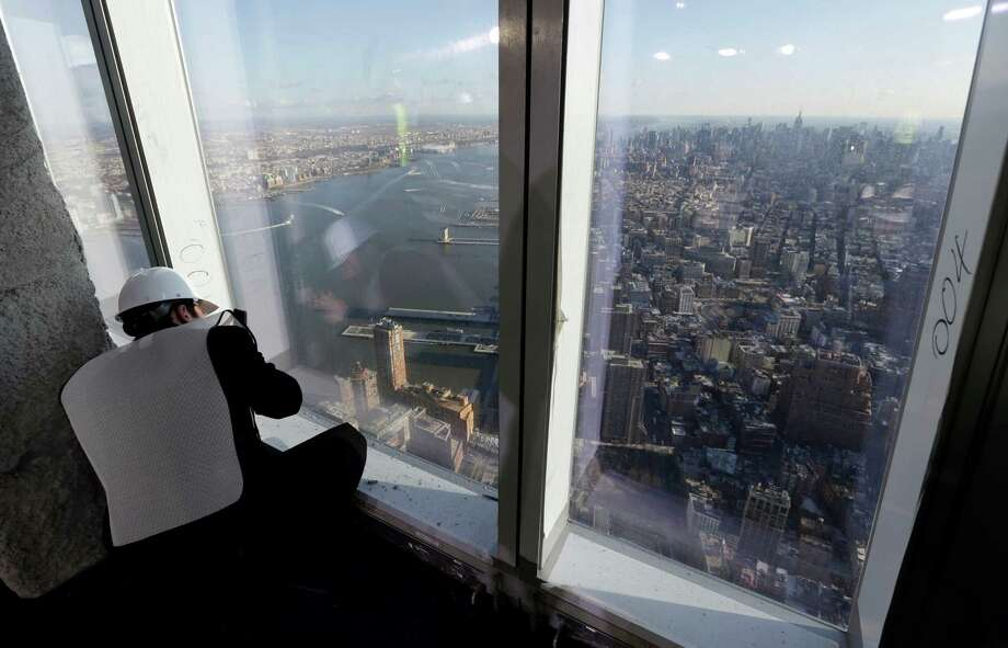 A member of the media takes a photograph of the Manhattan skyline from the unfinished observation deck on the 100th floor of the One World Trade Center building, under construction in New York, Tuesday, April 2, 2013. The observation deck will occupy the tower's 100th through 102nd floors. Elevators will whisk visitors to the top in just one minute but the experience of visiting the attraction will take an hour. Photo: Richard Drew, AP / AP