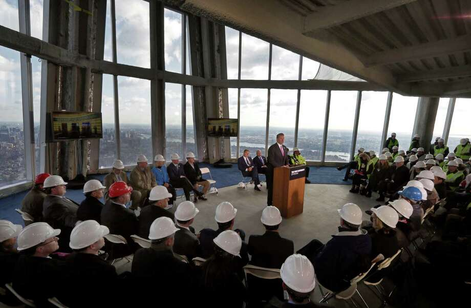 Legends Chairman & CEO David Checketts, at podium center, of the company that will run the observation deck on the 100th floor of the One World Trade Center building, address a news conference in the venue, in New York, Tuesday, April 2, 2013. The observation deck, that will not open until 2015, will occupy the tower's 100th through 102nd floors. Elevators will whisk visitors to the top in just one minute but the experience of visiting the attraction will take an hour. Photo: Richard Drew, AP / AP