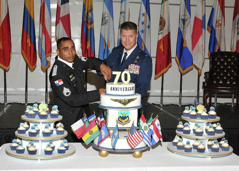 Sgt. Arnold Arias, left, a member of the Panamanian national police and U.S. Air Force Col. Marc Stratton, commandant, Inter- American Air Forces Academy, slice a cake during the Academy's 70th anniversary celebration at the IAAFA Airfield Training Complex, Joint Base San Antonio-Lackland. Photo: U.S. Air Force