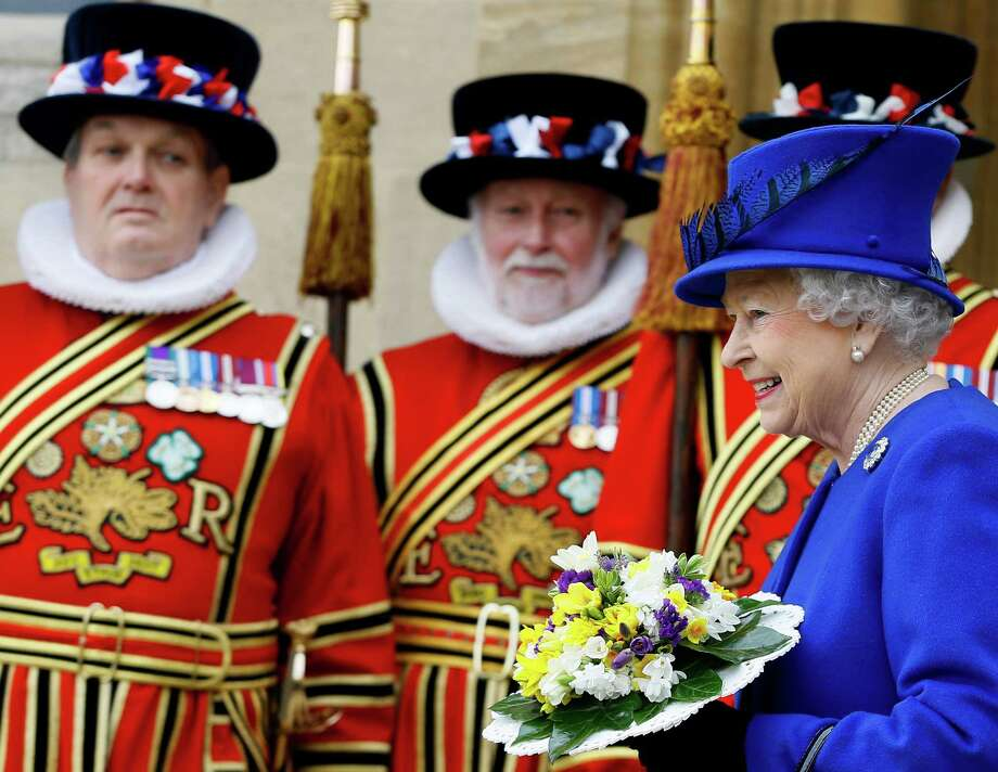 Britain's Queen Elizabeth II smiles as she walks past Yeoman of the Guard, after attending the Maundy service,  at Christ Church Cathedral in Oxford, England,  Thursday, March 28, 2013. During the service the Queen distributed the Maundy money to 87 women and 87 men, one for each of The Queen's 87 years. Each recipient receives two purses, one red and one white. The red purse will contain a 5 pound coin and 50 pence coin commemorating the 60th anniversary of The Queen's Coronation. The white purse will contain uniquely minted Maundy Money. This takes the form of silver one, two, three and four penny pieces, the sum of which equals the number of years the Monarch has years of age. This year there will be 87 pennies worth distributed. (AP Photo/Kirsty Wigglesworth, Pool) Photo: Kirsty Wigglesworth