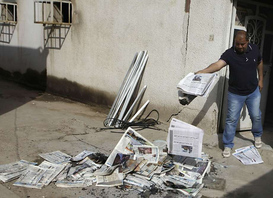 A man cleans up the offices of the Iraqi newspaper the Constitution in Baghdad after gunmen broke into the offices of four papers, stabbing and beating employees and damaging computers. Photo: Khalid Mohammed, Associated Press