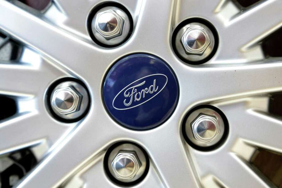 In this Wednesday, March 20, 2013 photo a Ford emblem is attached to the wheel of a sedan at a Ford dealership in, Norwood, Mass. March is turning out to be the best month for auto sales in at least six years.  Major automakers including Ford, Chrysler, Toyota, General Motors and Nissan all reported increases, with some reporting their best month since the start of the Great Recession in December of 2007.   (AP Photo/Steven Senne) Photo: Steven Senne
