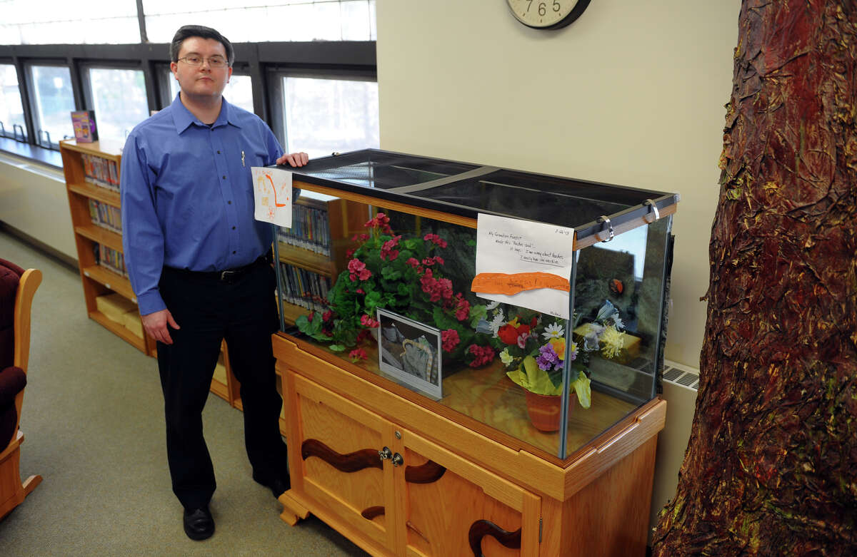 Shawn Fields, Branch Director at the Huntington Branch Library, stands next to the tank where Peaches the snake lived, on Tuesday April 2, 2013. Peaches lived for eight years at the branch but died recently after someone poured a cleaning solvent into her tank and onto her causing severe burns. The tank was converted into a memorial in her honor.