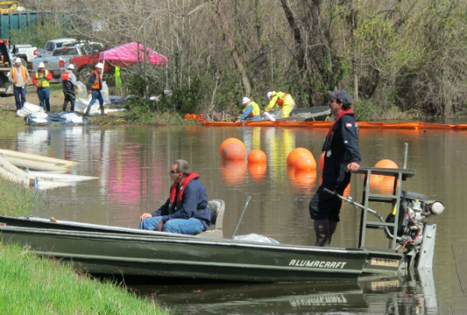 Crews work to protect Lake Conway, setting out containment booms and making additional checks on locations as they also begin cleanup and check wildlife in Mayflower, Ark., Sunday, March 31, 2013.