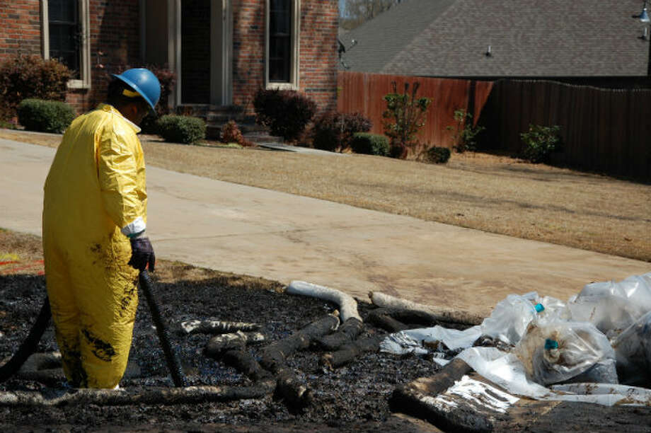 A worker cleans up oil in Mayflower, Ark., on Monday, April 1, 2013, days after a pipeline ruptured and spewed oil over lawns and roadways.