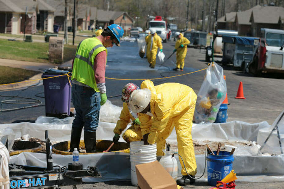A crew member with ExxonMobil washes oil from another crew member's boots at North Starlight Road in the Northwoods subdivision in Mayflower, Ark., Monday, April 1, 2013. Other crew members are seen power washing oil from the street near the pipeline that ruptured and dumped several thousands of barrels of oil Friday.
