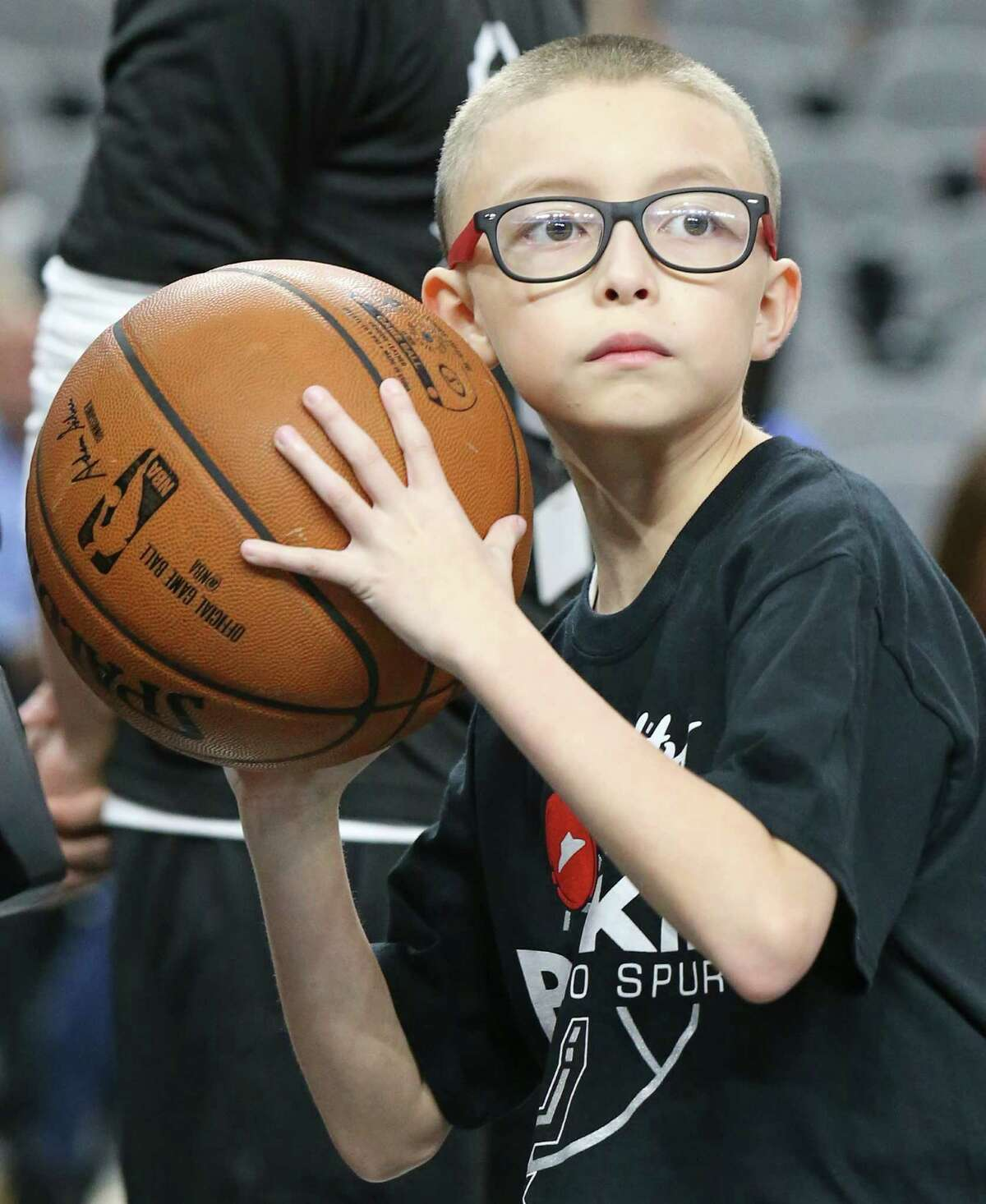 Ginobili San Miguel-Ramirez, 10, throws the ball to San Antonio Spurs players during warmups before the game with the Utah Jazz Monday Dec. 14, 2015 at the AT&T Center.