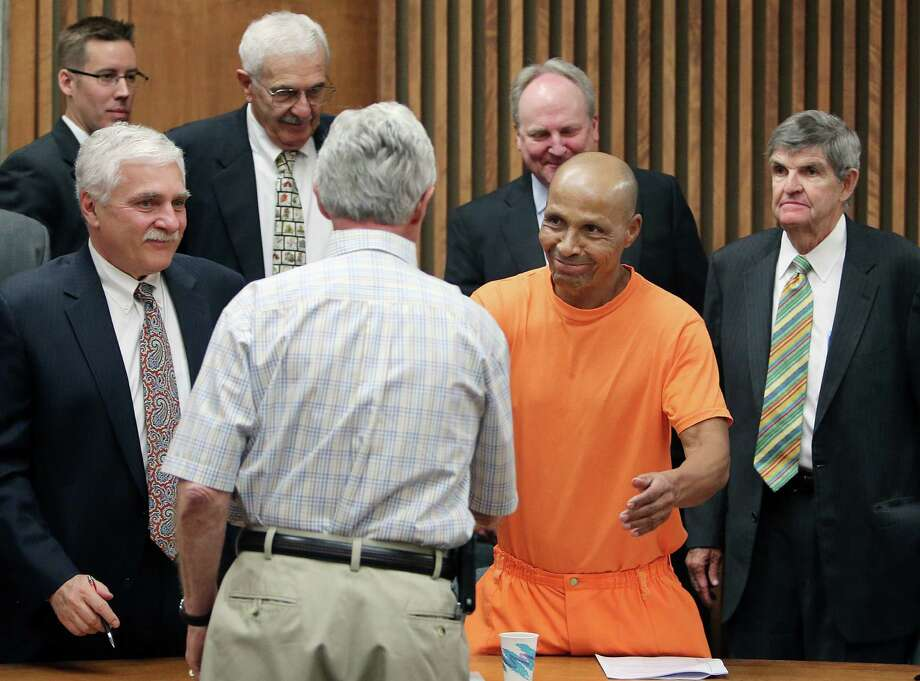 Lewis Taylor shakes the hand of his first attorney, Howard Kashman, as his current defense team surrounds him after a hearing that will result in his release. Photo: Benjie Sanders, POOL / Arizona Daily Star, Pool