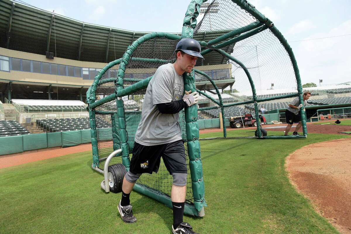 San Antonio Missions catcher Rocky Gale helps push the batting cage into position for a team workout at Nelson Wolff Stadium on Tuesday, April 2, 2013. The Missions open their Texas League schedule at home against Tulsa at 7:05 p.m. on April 4.