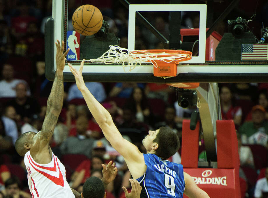 Orlando center Nikola Vucevic gets tangled in the net as he contest a shot by Rockets power forward Thomas Robinson. Photo: Smiley N. Pool, Houston Chronicle / © 2013  Houston Chronicle