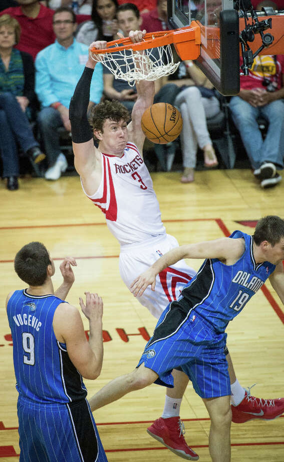 Rockets center Omer Asik dunks the ball over Magic point guard Beno Udrih. Photo: Smiley N. Pool, Houston Chronicle / © 2013  Houston Chronicle