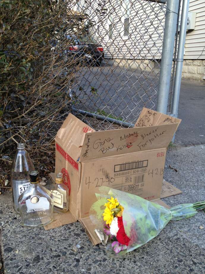 A make-shift memorial is left Tuesday near the driveway where a man fatally shot by a Bridgeport police officer fell.