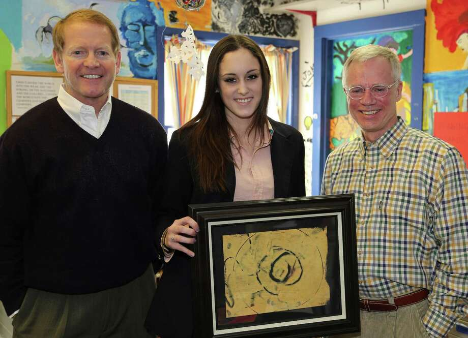 Paul Doherty, left, and Dave Behnke of the Behnke Doherty Gallery in Washington Depot share time with Glenholme School student Annabel, who holds a monoprint by fellow student-artist Courtney that is part of the Glenholme student art exhibit and auction at Marty's Café  in Washington this month.  Courtesy of Devereux Glenholme School Photo: Contributed Photo / The News-Times Contributed