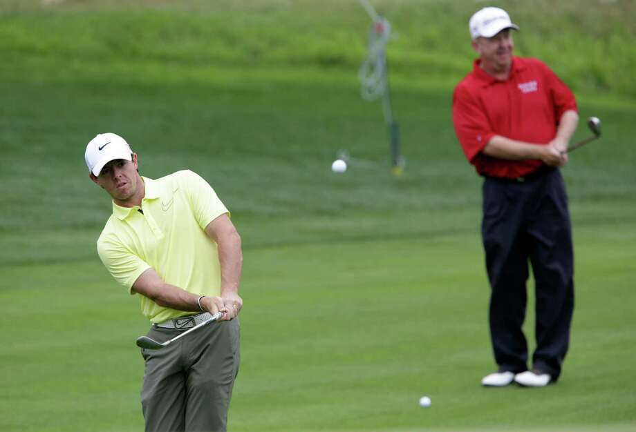 Rory McIlroy, left, chips to a green as he plays a warmup round with Billy Mayfair, right, at the 2013 Valero Texas Open at the AT&T Oaks Course on Tuesday, April 2, 2013. Photo: Bob Owen, San Antonio Express-News / ©2013 San Antonio Express-News