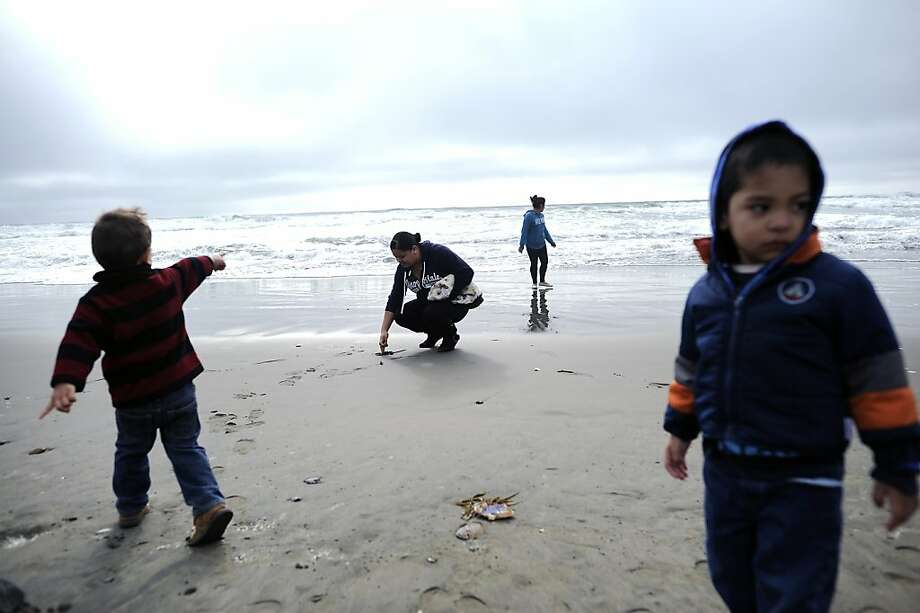 Visiting the city from Concord, 2-year-old Adrian Carta (left) and mom Jasmine play in the sand on the water's edge at Ocean Beach in San Francisco with Ivonne Chavez and her son Munel, 2. Photo: Michael Short, Special To The Chronicle