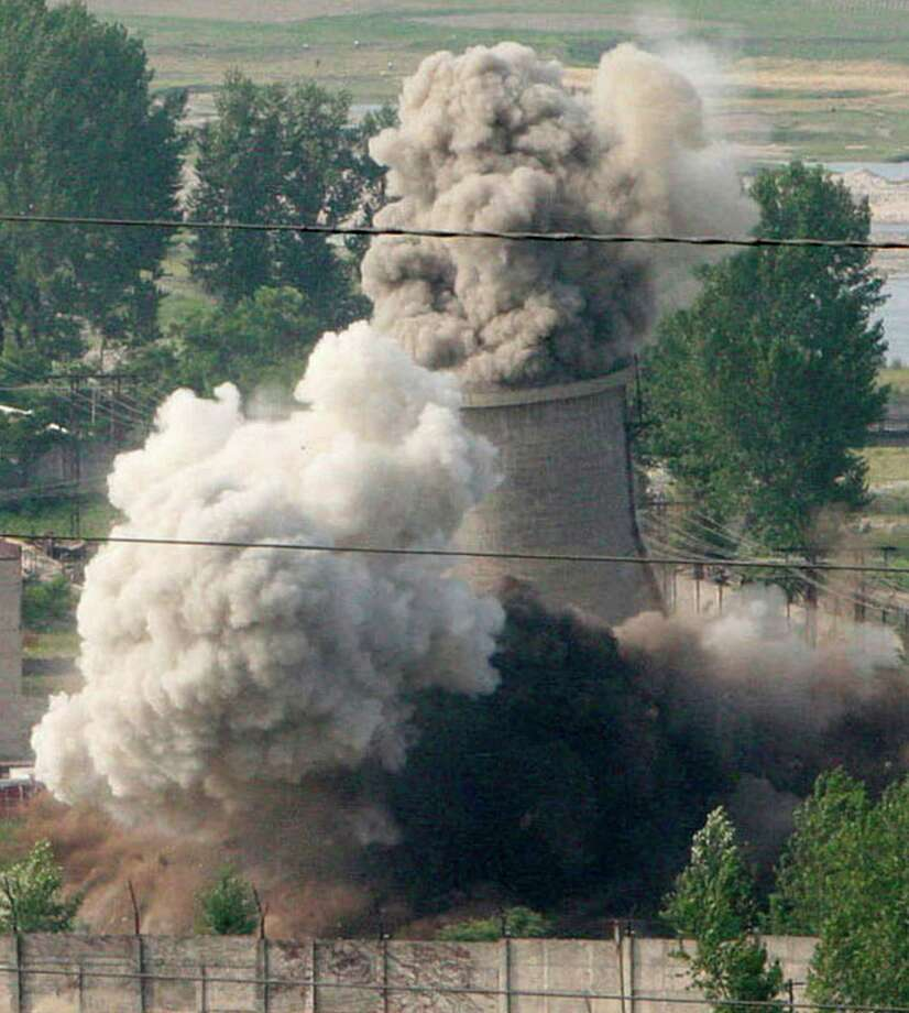 FILE -  In this June 27, 2008 file photo released by China's Xinhua News Agency, the cooling tower of the Nyongbyon nuclear complex is demolished in Nyongbyon, also known as Yongbyon, North Korea.   North Korea vowed Tuesday, April 2, 2013,  to restart a nuclear reactor that can make one bomb's worth of plutonium a year, escalating tensions already raised by near daily warlike threats against the United States and South Korea. The North's plutonium reactor was shut down in 2007 as part of international nuclear disarmament talks that have since stalled. The declaration of a resumption of plutonium production — the most common fuel in nuclear weapons — and other facilities at the main Nyongbyon nuclear complex will boost fears in Washington and among its allies about North Korea's timetable for building a nuclear-tipped missile that can reach the United States, technology it is not currently believed to have.   (AP Photo/Xinhua, Gao Haorong, File) NO SALES Photo: Gao Haorong