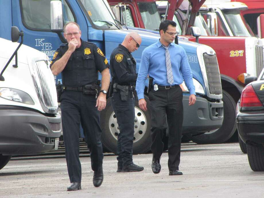Police walk away from the cab of a tractor-trailer where a man's body was found. The rig hadn't moved from a lot on Ackerman Road at Interstate 10 in more than 24 hours. Photo: Eva Ruth Moravec / San Antonio Express-News