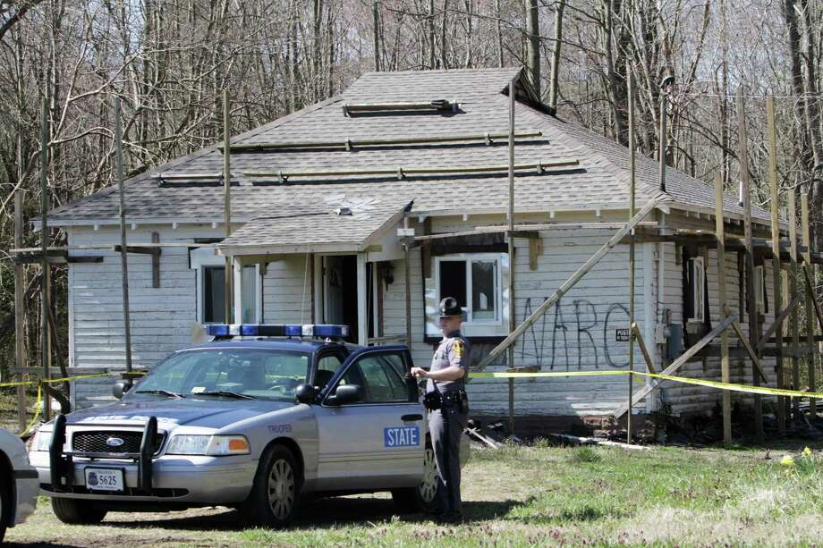 A state trooper stands guard in front of a house on Airport Drive in Melfa, Va. on Tuesday, April 2, 2013. One of two people being questioned about a fire at the house  has been charged in the blaze.  Tonya Susan Bundick, of Parksley, Va.,was charged this morning with one count of felony arson and one count of felony conspiracy to commit arson, said state police spokeswoman Corinne Geller.  ( Steve Earley / The Virginian-Pilot )  (AP Photo/The Virginian-Pilot, Stevve Earley)  MAGS OUT Photo: Steve Earley
