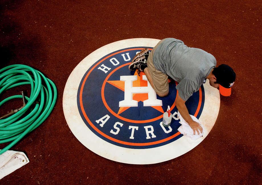 Kyle Edlemon cleans the on-deck circle before the start of the second game of the Astros' season-opening series against the Rangers. Photo: Cody Duty / © 2013 Houston Chronicle