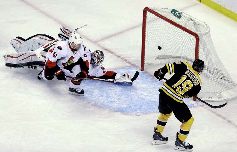 Boston Bruins center Tyler Seguin puts the puck in the net past Ottawa Senators goalie Robin Lehner (40) and left wing Andre Benoit (61) in the first period of an NHL hockey game in Boston, Tuesday, April 2, 2013. (AP Photo/Elise Amendola) Photo: Elise Amendola