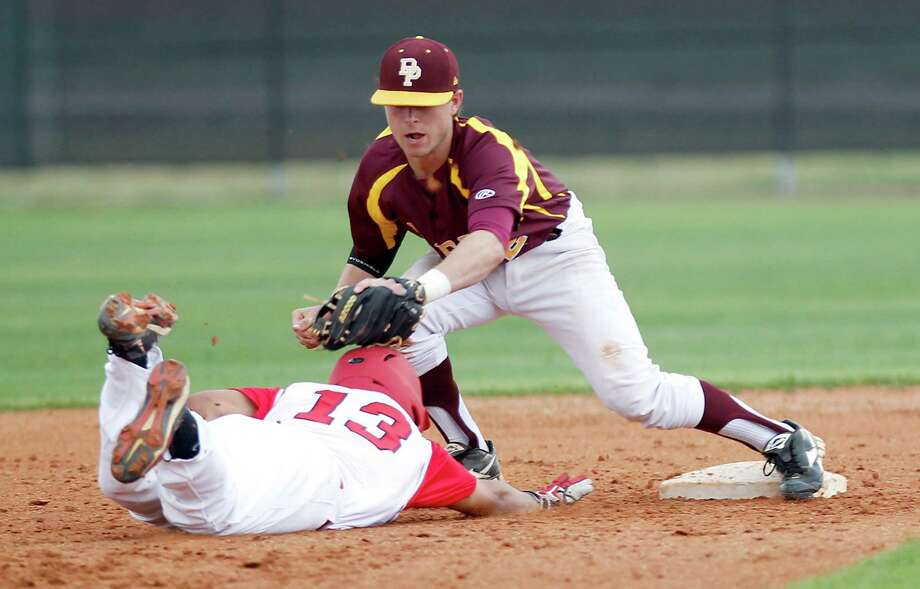 Deer Park's Clay Thompson applies the tags to catch North Shore's Xavier Leal on a pickoff play. Photo: Thomas B. Shea / © 2013 Thomas B. Shea