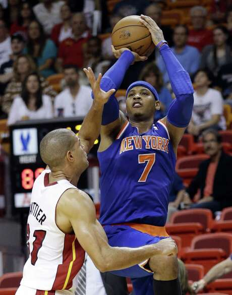 The Knicks' Carmelo Anthony shoots over the Heat's Shane Battier en route to tying his career high of 50 points during New York's win in Miami. Photo: Wilfredo Lee / Associated Press