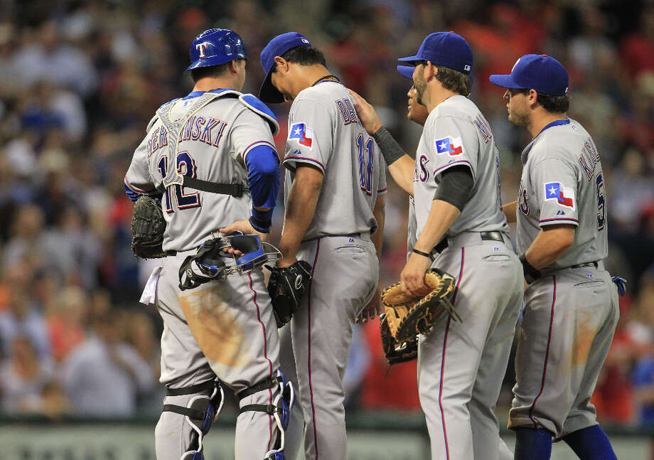 Teammates of Rangers pitcher Yu Darvish console him after he gave up his first and only hit of the game to the Astros. Photo: Karen Warren / © 2013 Houston Chronicle