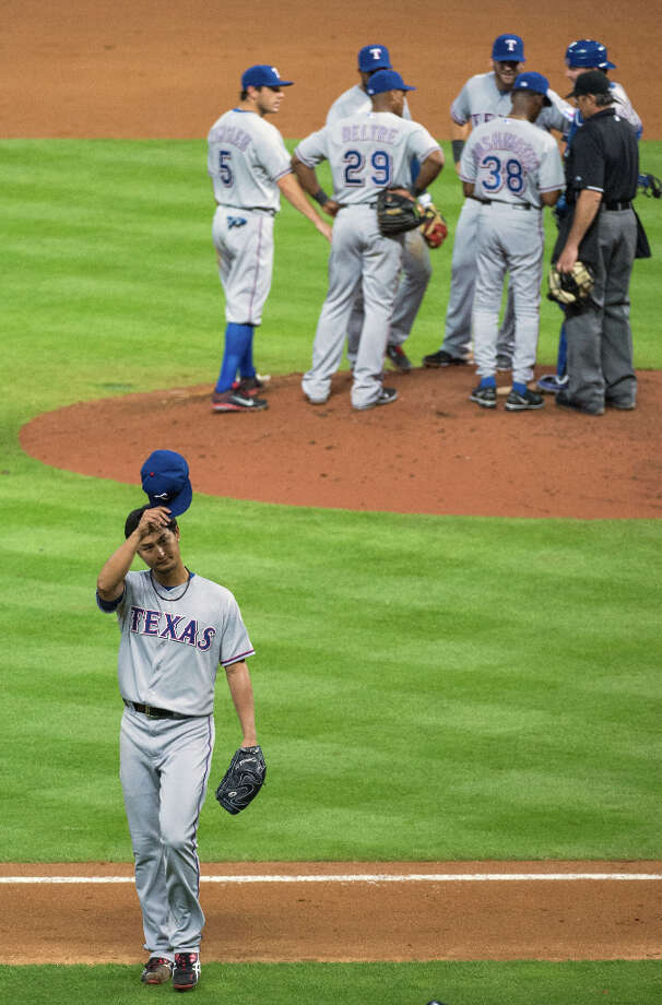 Rangers pitcher Yu Darvish tips his cap to the crowd as he leaves the game after surrendering a hit to the Astros. Photo: Smiley N. Pool / © 2013  Smiley N. Pool
