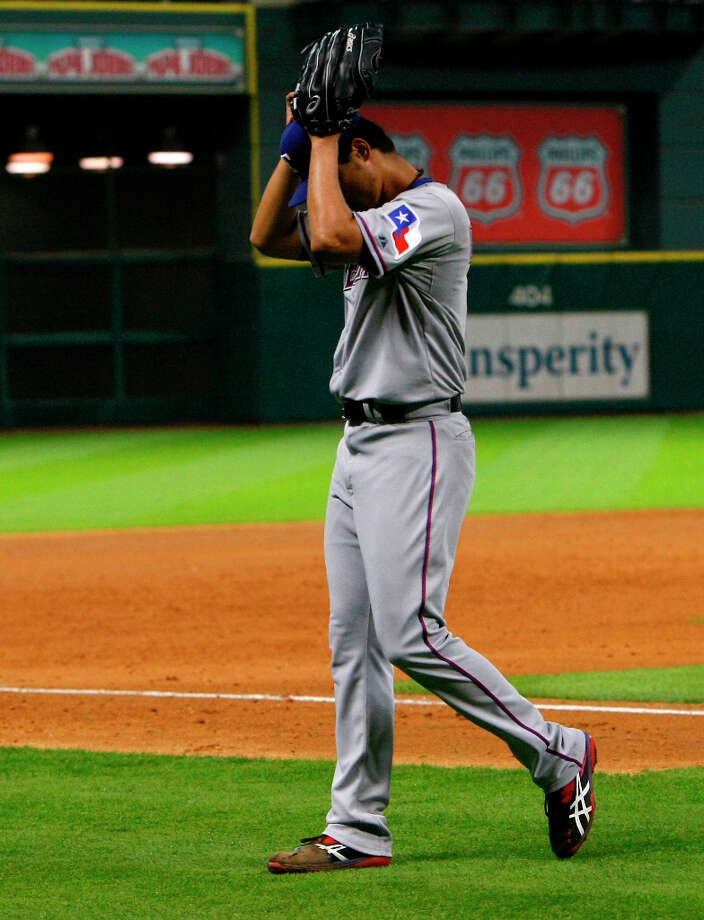 Rangers pitcher Yu Darvish adjusts his hat while leaving the field after almost completing a perfect game against the Astros. Photo: Cody Duty / © 2013 Houston Chronicle