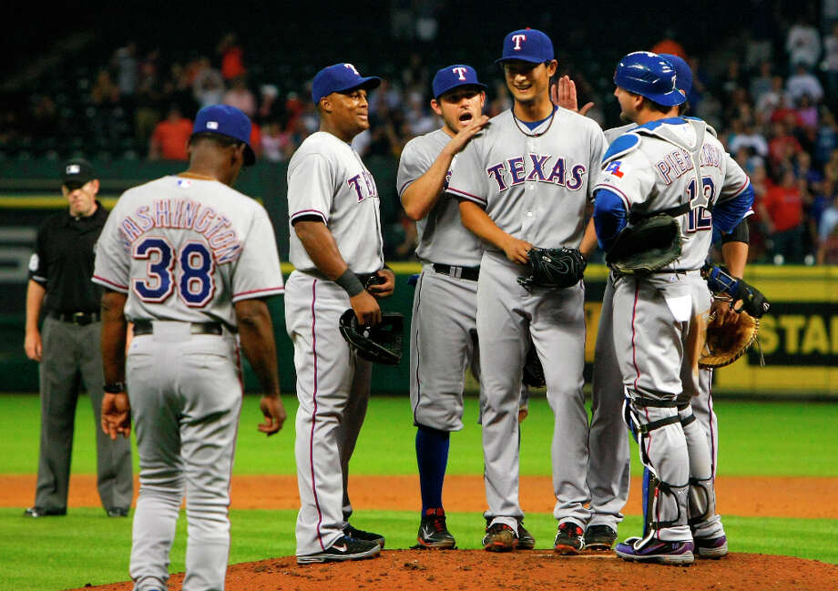 Rangers pitcher Yu Darvish smiles after allowing the Astros' first hit. Photo: Cody Duty / © 2013 Houston Chronicle