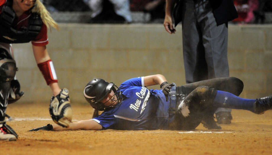 New Caney senior first baseman Kindell Gainer slides home ahead of the tag by Crosby junior catcher Ariel Clogston in the top of the 6th inning of their District 19-4A matchup at Crosby High School on Tuesday. Photo: Jerry Baker, For The Chronicle