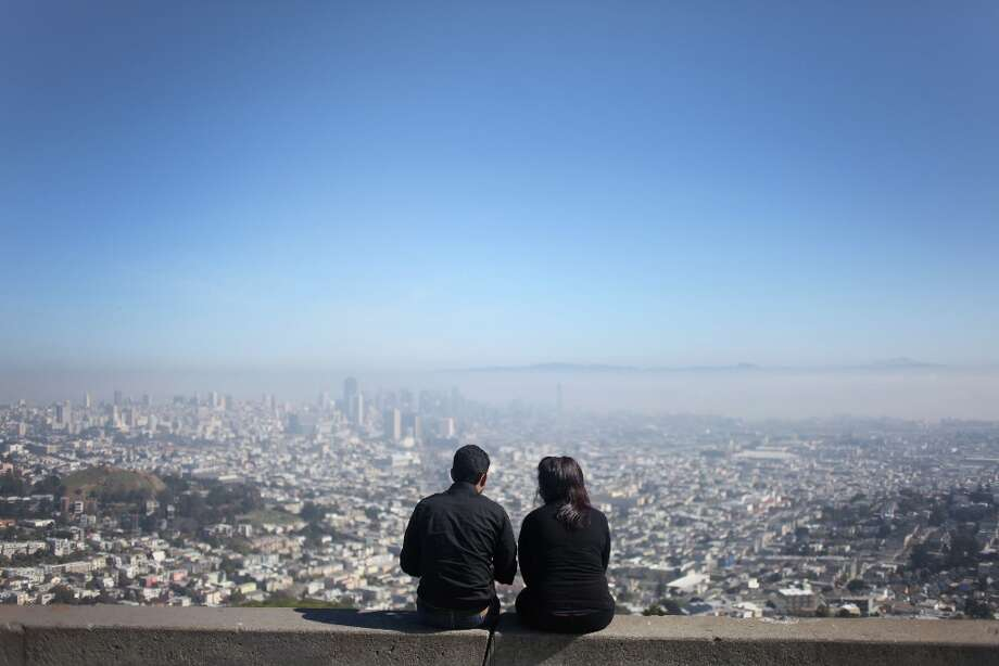 A couple looks at the downtown skyline at Twin Peaks on March 12, 2013 in San Francisco, Calif. The two individuals declined to give their names. Photo: Pete Kiehart, The Chronicle / ONLINE_YES