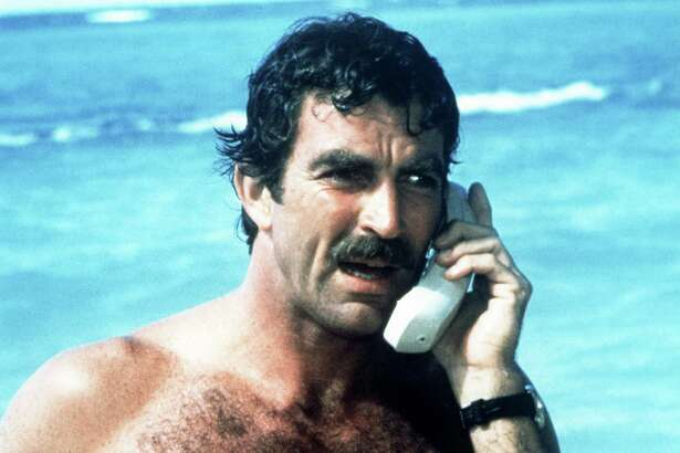American actor Tom Selleck as Thomas Magnum, making a mobile phone call from the beach, in the American TV series 'Magnum PI', circa 1985. (Photo by Silver Screen Collection/Getty Images)