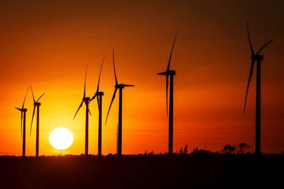 The sun sets behind several 285ft tall 2.5 MW Clipper wind turbines at the BP Sherbino Mesa II Wind Farm, Monday, Feb. 20, 2012, in Fort Stockton. After cutting its solar program last year, BP is beefing up its investments into wind energy and recently launched its fourth Texas wind farm, in Fort Stockton. On 20,000 acres in Pecos County, the Sherbino II farm has 60 wind turbines to generate enough electricity to power more than 175,000 homes. ( Michael Paulsen / Houston Chronicle ) Photo: Michael Paulsen / © 2012 Houston Chronicle
