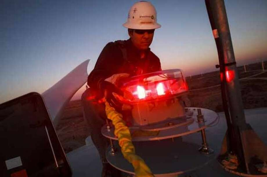 Manny Dominguez, Deputy Facility Manager of the BP Sherbino Mesa II Wind Farm, checks the FAA light while working 285ft in the air atop turbine 53, BP's 1000th wind turbine, Monday, Feb. 20, 2012, in Fort Stockton. After cutting its solar program last year, BP is beefing up its investments into wind energy and recently launched its fourth Texas wind farm, in Fort Stockton. On 20,000 acres in Pecos County, the Sherbino II farm has 60 wind turbines to generate enough electricity to power more than 175,000 homes. Photo: Michael Paulsen, Houston Chronicle / © 2012 Houston Chronicle