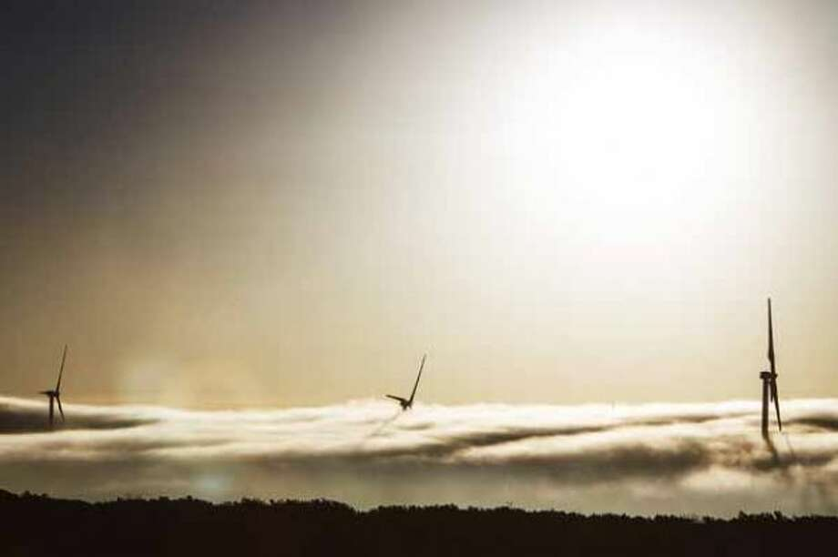 A thick cloud of fog and morning light engulfs several 285ft tall 2.5 MW Clipper wind turbines at the BP Sherbino Mesa II Wind Farm, Monday, Feb. 20, 2012, in Fort Stockton. After cutting its solar program last year, BP is beefing up its investments into wind energy and recently launched its fourth Texas wind farm, in Fort Stockton. On 20,000 acres in Pecos County, the Sherbino II farm has 60 wind turbines to generate enough electricity to power more than 175,000 homes. ( Michael Paulsen / Houston Chronicle ) Photo: Michael Paulsen / © 2012 Houston Chronicle