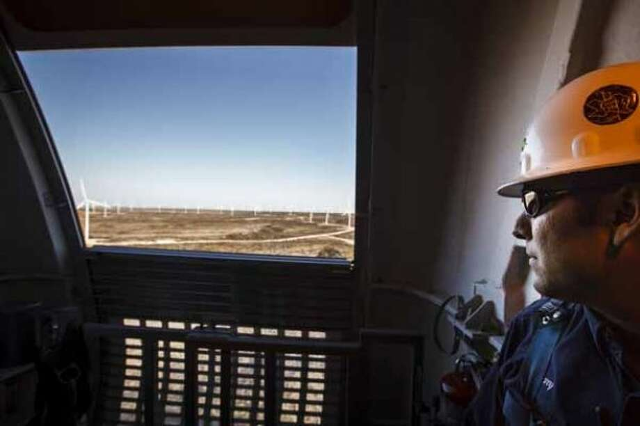 Manny Dominguez, Deputy Facility Manager of the BP Sherbino Mesa II Wind Farm, looks out as he opens the garage door from 285ft atop turbine 53, BP's 1000th wind turbine, Monday, Feb. 20, 2012, in Fort Stockton. After cutting its solar program last year, BP is beefing up its investments into wind energy and recently launched its fourth Texas wind farm, in Fort Stockton. On 20,000 acres in Pecos County, the Sherbino II farm has 60 wind turbines to generate enough electricity to power more than 175,000 homes. Photo: Michael Paulsen, Houston Chronicle / © 2012 Houston Chronicle