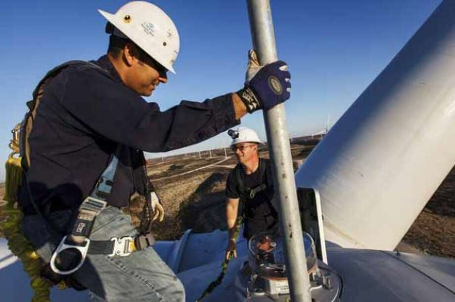 Manny Dominguez, Deputy Facility Manager of the BP Sherbino Mesa II Wind Farm, (left) and James Hultman, Lead Technician, climb atop turbine 53, BP's 1000th wind turbine, 285ft in the air, Monday, Feb. 20, 2012, in Fort Stockton. After cutting its solar program last year, BP is beefing up its investments into wind energy and recently launched its fourth Texas wind farm, in Fort Stockton. On 20,000 acres in Pecos County, the Sherbino II farm has 60 wind turbines to generate enough electricity to power more than 175,000 homes. Photo: Michael Paulsen, Houston Chronicle / © 2012 Houston Chronicle