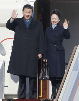 FILE - In this March 22, 2013 file photo, Chinese President Xi Jinping, left, and his wife Peng Liyuan wave upon their arrival to the government airport Vnukovo II, outside Moscow. China's elegant new first lady's choice of attire has sparked a flurry of excitement over an independent homegrown label, an unusual phenomenon in a country where political figures are more fuddy-duddy than fashionable and wives usually shy away from the spotlight. (AP Photo/Ivan Sekretarev, File)