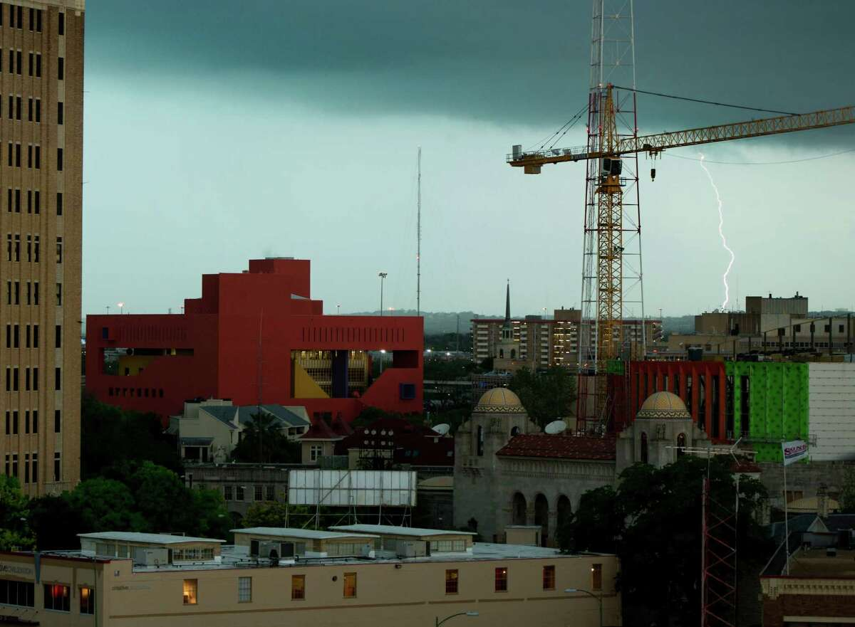 Lightning is seen behind a construction crane as storm clouds move through downtown San Antonio, Wednesday, April 3, 2013.