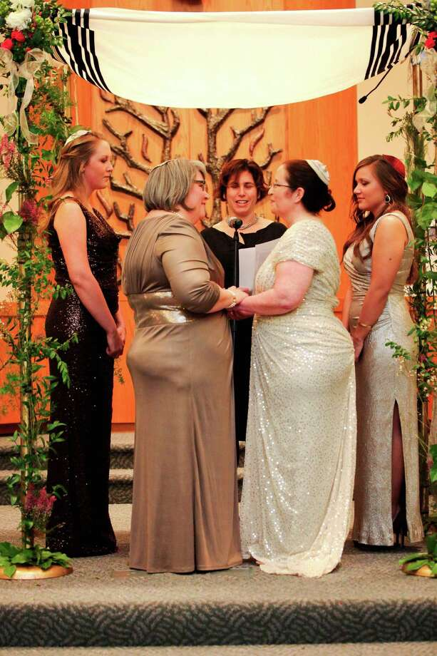 This January 19, 2013 photo shows Shelly Crocker, second left, and Sandy Kibort, second right, with Rabbi Jill Borodin, center, during their wedding, with their daughters, Emma Kibort-Crocker, left, and Hannah Kibort-Crocker, right, at Congregation Beth Shalom in Seattle, Wash. The wedding couple stands under a huppah, a traditional Jewish wedding canopy. Washington State voters approved same sex marriage with the passing of Referendum 74 in November, 2012. Photo: Shelly Crocker, Sarah Vanausdoll