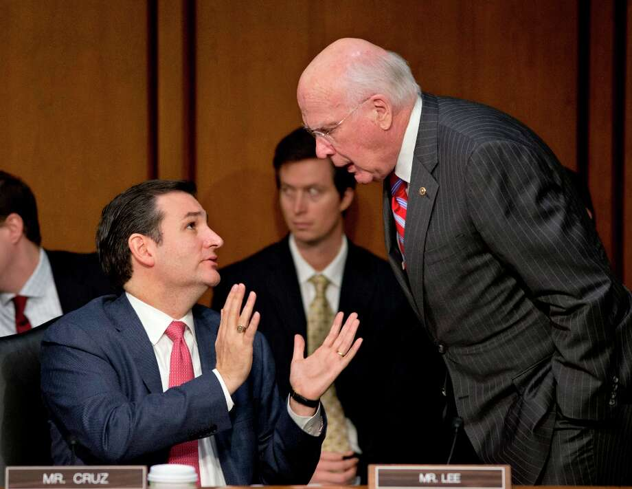 FILE – In this January 30, 2013 file photo Senate Judiciary Committee Chairman, Sen. Patrick Leahy, D-Vt., speaks with freshman Republican Sen. Ted Cruz of Texas, left, about what lawmakers should do to curb gun violence during a Judiciary committee hearing on Capitol Hill. Leahy, 72, has served nearly four decades in the upper chamber, and earned his perch as one of the Senate's most powerful, and visible, members. Now he is front and center in two of the most contentious fights facing a bitterly divided Senate: guns and immigration. (AP Photo/J. Scott Applewhite, File) Photo: J. Scott Applewhite, Associated Press / AP