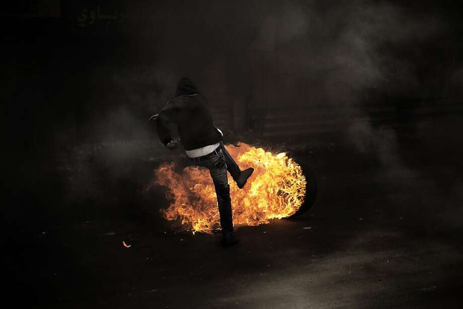A Palestinian demonstrator kicks a flaming tire during clashes with Israeli soldiers in Hebron. Photo: Marco Longari, AFP/Getty Images